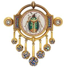 Antique Gold and Micromosaic Fringe Pendant-Brooch  Centering a circular white tesserae panel depicting a multicolored tesserae beetle accented by gold, encircled by red and white tesserae, within a double row of rope-twist gold, flanked and tipped by rectangular and circular panels decorated with multicolored tesserae in a geometric pattern, suspending a seven strand gold fringe tipped by gold balls set with blue, red and white tesserae florets, reverse with glazed compartment, with Papal…