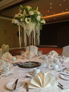 Martini glass arrangement.White rose and lily flowers set on gel pearls with pearl swag.