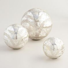 Crafted of blown glass with a mercury finish, our silver spheres are hand etched with intricate floral designs for a delicate, antique-inspired look. Display them standing on their small flat bases or piled in a decorative bowl.
