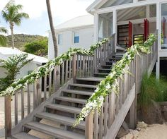 Delphinium branches and greens are draped on a staircase leading to the beach.