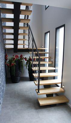 Escalier limon central, marches en bois et garde corps en acier peint.