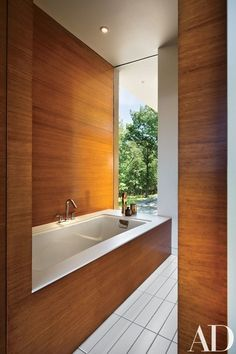 The master bath's Tea-for-Two tub by Kohler is encased in bamboo, with Corian trim. Lingotto ceramic tile from Nemo paves the floor | archdigest.com