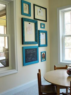 A mini art gallery of coordinating frames with metal clips for displaying children's artwork.