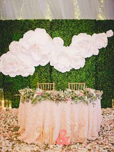 A big and bold custom party backdrop featuring your monogram, a big panel of fabric that matches your wedding style or even a faux greenery wall filled with candles can provide your reception with a fun focal point. Bonus: One of these can double as a background for your photo booth.