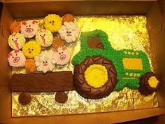 Tractor cake with farm animal cupcakes.
