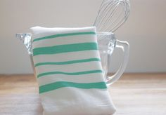 See how a bit of paint, fabric medium and tape can transform basic flour sack towels from boring to beautiful.