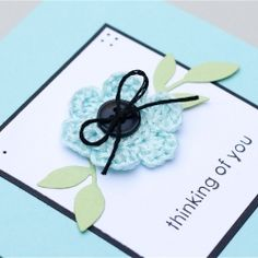 A cute little crocheted flower takes center stage on this stylish handmade card.