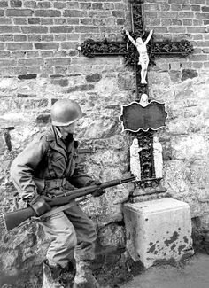 A US soldier of the 83rd Infantry Division near a roadside crucifix in Belgium, World War II, 25th December 1944. (Photo by Tony Vaccaro/Getty Images)