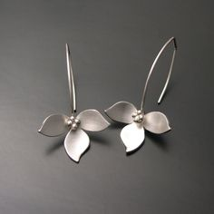 "Lotus petals dangle behind silver bead center. Sterling with sterling ear wires. Approx 2"" long x 1"" wide."