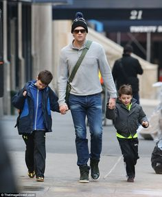 Doting dad: Tom kept a tight grip on his sons John, left, and Benjamin, right, as they str...