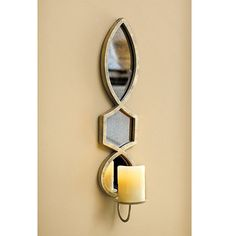 Our Elise candle sconce adds flickering romance to any space. The narrow frame is crafted of iron with three jewel-shaped, lightly antiqued mirrors.