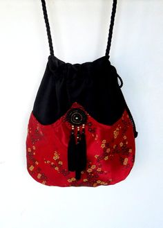 Perfect bag for the free spirited lady. It has the richness of the red satin pocket in front with a black medallion and three small tassels. The
