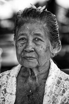 Faces of Bali, old woman, lines of life, lady, proud, a face that have lived with many stories to tell, beauty, flower, intense eyes, strong image, aged, worn, portrait, photo b/w.
