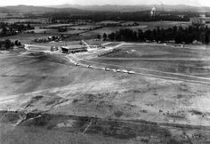A June 1941 aerial view looking southwest at Sky Harbor hangar, showing the hangar & terminal, and over a dozen military aircraft on the field.