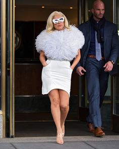 Lady Gaga rocks a dramatic fur topper, sleek white skirt and glam white sunglasses