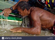 A Brazilian fisherman pushing the boat manually among waves on the beach