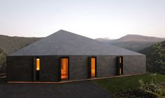 """Mottled grey tiles envelop this angular house in the Swiss Alps, which was designed by Milanese firm JM Architecture to look """"like a stone in the landscape"""""""
