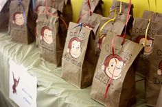 "Curious George Birthday Party Favor Bags.  Cute monkey, personalized ""Curious XYZ"" for each guest.  Balloon tied on top."