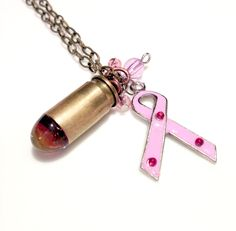 """Shoot down Breast Cancer!  Winchester .45 ACP bullet shell casing with fuchsia lampwork glass bullet, pink accent beads, and a breast cancer awareness ribbon charm.  The bullet was carefully removed using a specialized tool, and the glass bead made directly inside the brass case.  20"""" Antiq..."""