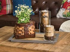 Turn a fishing creel into a host for a simple bouquet and arrange it on a tray with bark-coated candles for a lodge-inspired floral display.