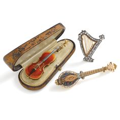 Gold instrument brooches. Violin and harp are English, 1890. Lute is French, 1850. Guilloche and old mine cut diamond elements.