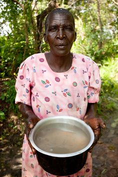 A woman in rural Uganda shows her old water source. (photo: Esther Havens)