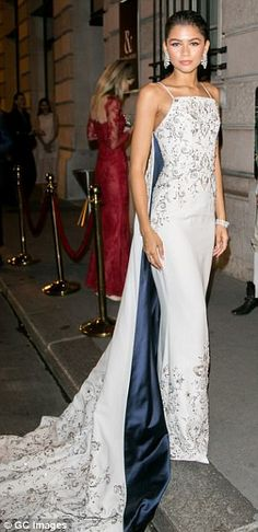 Gorgeous:The 20-year-old showed off her slender figure in the white dress, complete with a lengthy train, as she arrived at a lavish Paris Fashion Week bash with Arizona Muse (R)