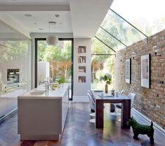 modeles de cuisine, exemple cuisine blanche avec ilot central et mur en briques, parque bois foncé, toiture en verriere