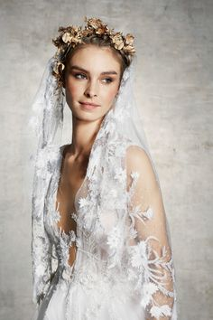 Wedding dress with plunging neckline and embroidered bodice shown with veil