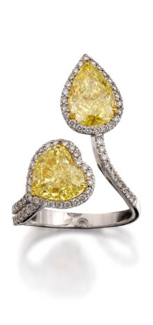 COLOURED DIAMOND AND DIAMOND RING Of toi et moi design with cluster terminals, one claw-set with a pear-shaped diamond of yellow hue weighing 2.15 carats framed by brilliant-cut near colourless diamonds, the other similarly set with a heart-shaped diamond of yellow hue weighing 2.32 carats between split shoulders pave-set with colourless diamonds, mounted in 18ct gold