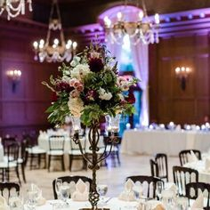 Tall floral centerpiece consisting of dusty pink roses, burgundy roses, white hydrangeas, and greenery sitting atop an iron candle stand   Leslie Ann Photography   villasiena.cc