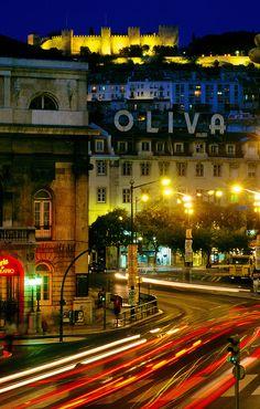 Flujos de tráfico en frente de la Plaza Rossio (plaza) con Castelo de Sao Jorge (castillo) en el fondo, Lisboa, Portugal