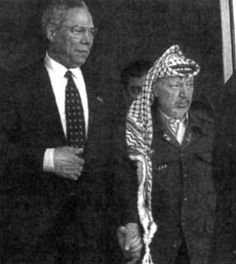 Former Secretary of State Colin Powell holds hands with PLO leader Yasser Arafat as he covertly places his right hand in his coat, a sign to other initiates. Powell is a 33rd degree Mason and a Council on Foreign Relations alumnus. The late Arafat was also a member of the Masonic Lodge.