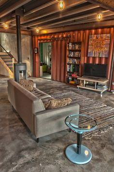 shipping container house--family room, so awesome!! love the barn door!!