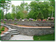 Pavers and retaining walls can be a great way of managing a front yard slope. Design by Boyden's Landscaping in Pelham, NH.