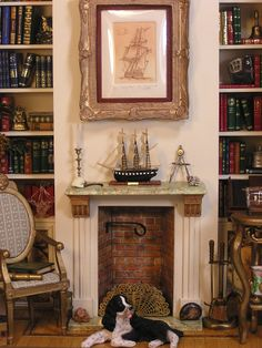 """The Captain's Library, club project Miniatures West ~ center. Scratch built fireplace with an excellent carved wood sailing ship and sextant on the mantle. The framed picture over the fireplace is a signed and numbered limited edition print of an etching entitled """"Sailing Home"""" by John Anthony Miller. It is number 10/100."""