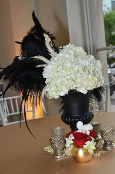 1920s Gatsby Centerpiece: Large black urn filled with White Hydrangea and black ostrich, rooster, and pheasant feathers with a smaller gold globe of red roses and white Dendrobium orchids for a Gatsby 1920s Speakeasy theme | by Andrea Layne Floral Design (www.andrealaynefloraldesign.com)