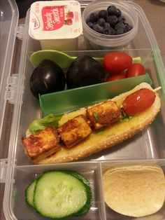 Cottage cheese skewer on a bread roll, yogurt, fruits, veggies and crisps.