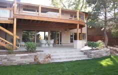 A stone patio and an elevated patio together create unique and separate spaces for outdoor entertainment. By Native Edge Landscapes in Boulder, Colorado.