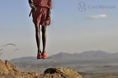 A Maasai Warrior jumps whilst wearing red Crocs he bought for a dollar at the market.