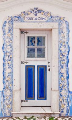 Beautiful tile frame around door. Sign over door translated 'Casino source of home'. In Ericeira, Portugal