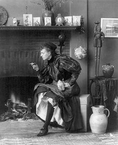 Frances Benjamin Johnston -  Frances Benjamin Johnston, full-length portrait, seated in front of fireplace, facing left, holding cigarette in one hand and a beer stein in the other, in her Washington, D.C. studio, 1896