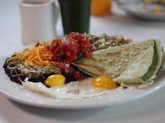 Succotash's eclectic vibe can be seen in everything from the eight-layer citrus cake with teal frosting to their artistic, kitschy decor. For breakfast, locals love the pork hash with sides of black beans and potatoes. Guy says of this spicy plate,