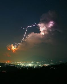 lightning storm over bright city at night colorful orange lavender clouds