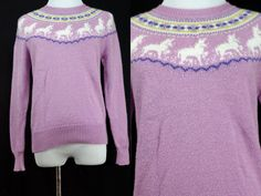 So cute! Little white unicorns circle around the neckline of this soft purple/lavender sweater. Yellow and turquoise highlights. Made of stretchy