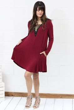 Long sleeve dress with lace up neckline. Super soft, stretchy fabric. Contrast lace up in black with string laced between. So cute and right on trend! Side pockets. Loose fit. Burgundy in color.