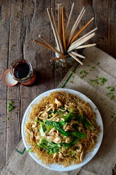 Pan-fried noodles with chicken and leafy greens.