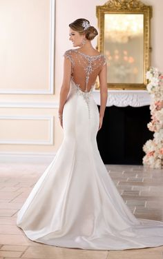 From Stella York, this cap sleeve fit and flaire wedding dress with beaded illusion back is an absolute stunner! Pearl Mikado fabric in a fit-and-flare silhouette brings the drama to any wedding ceremony. Slim lines create a glamorous hourglass shape while modern moonstone bead work catches the light and flatters the neckline. The beading of the cap sleeves continues onto the open, illusion back and around the bodice. Stella crystal buttons over an easy close zipper finish this very…