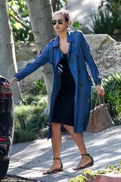 Busy day: Irina wore a long blue shirt over a black dress as she ran her errands in the late afternoon before picking up dinner, presumably for her and Bradley
