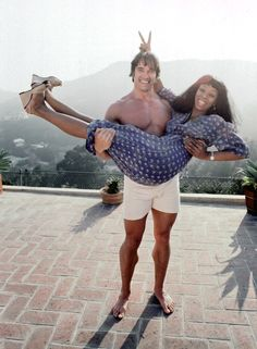 """Queen of Disco"" Donna Summer gets a lift from body builder, future movie star and politician Arnold Schwarzenegger at her home in April 1977 in Los Angeles, California. Get premium, high resolution news photos at Getty Images"